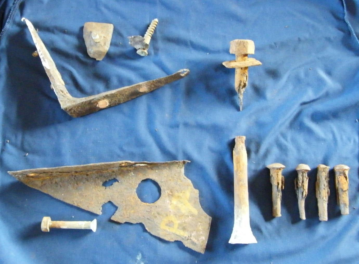 Fastenings removed from the hull. The items to the left indicate how fittings that are less noble, steel and iron, can corrode whilst their fastenings of copper and bronze remain intact. The large bolt is one of ten that secures the ballast keel to the hull. The mid section has corroded away. The four fastenings, bottom right, are wrought iron bolts removed from the gunwhales.