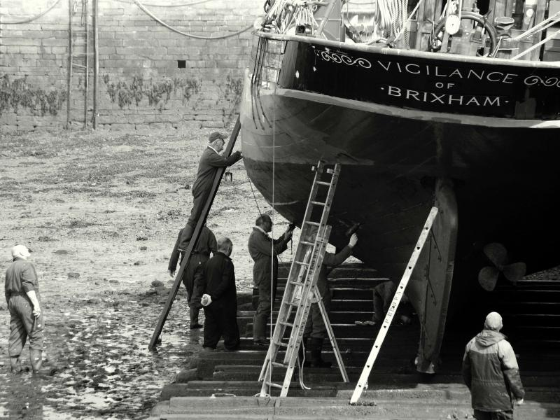 Black and white image of men working on a vessel taken by Peter Hunt